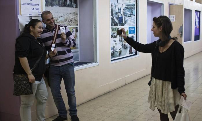 Uma mulher tira uma foto de um casal segurando cédulas do lado de fora de uma seção eleitoral em Tel Aviv NIR ELIAS / REUTERS