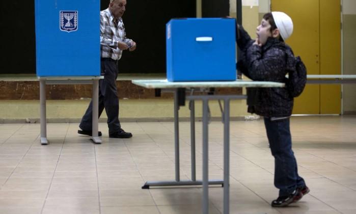 Um menino israelense observa uma urna enquanto um homem se prepara para votar MENAHEM KAHANA / AFP