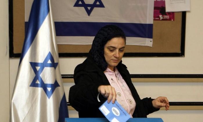 Uma mulher deposita seu voto em meio a bandeiras de Israel GALI TIBBON / AFP