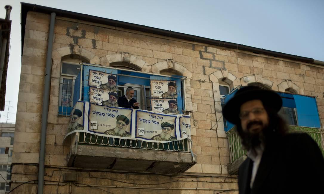 Um israelense caminha em frente a uma casa com várias fotos do líder espiritual judeu Rabbi Ovadia Yosef, do partido Shas Sebastian Scheiner / AP