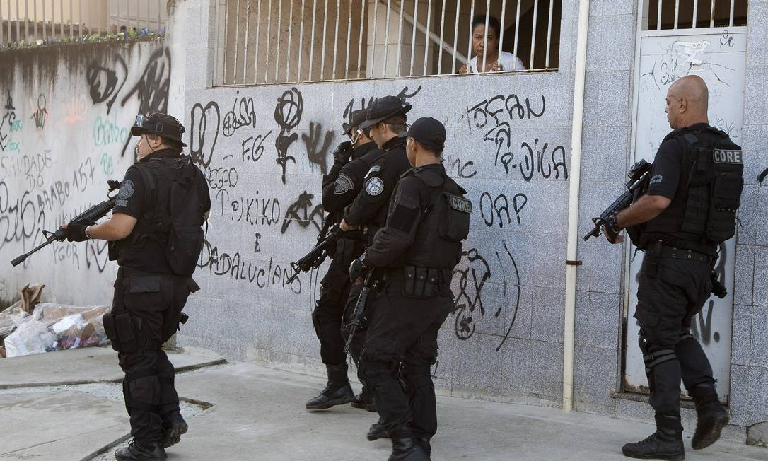 Moradora observa ação dos policiais civis na comunidade Fernando Quevedo / Agência O Globo