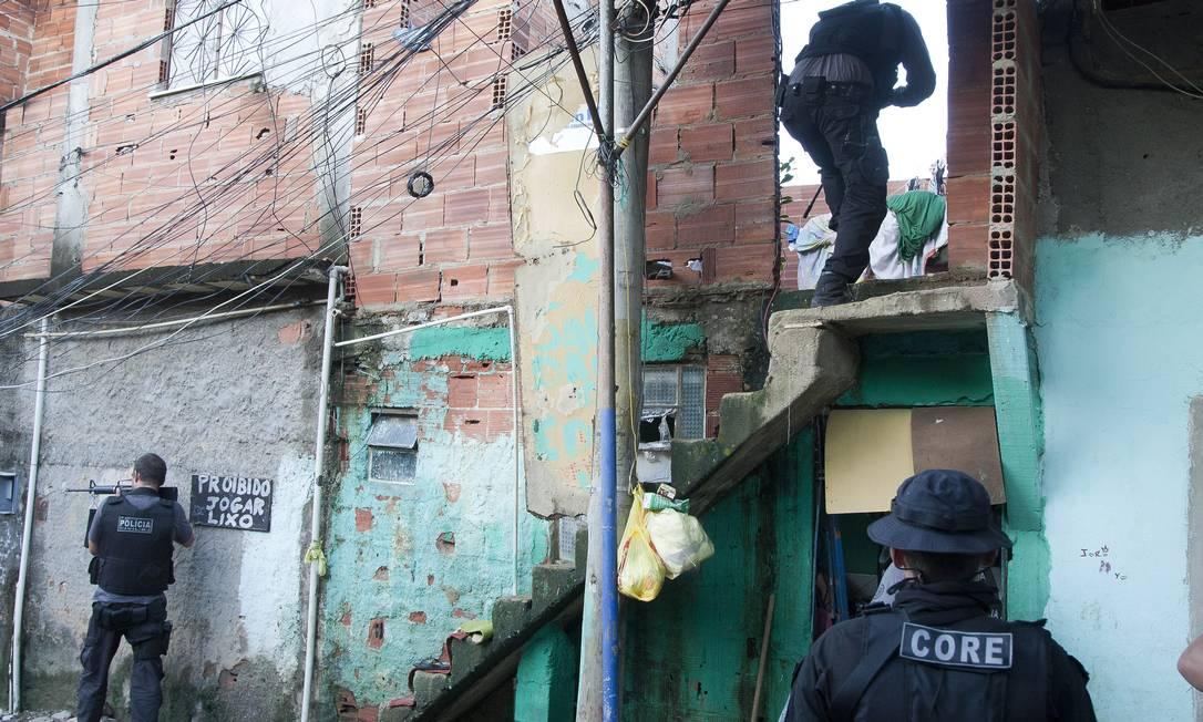 Policiais vasculham becos e lajes na Favela do Dique Fernando Quevedo / Agência O Globo