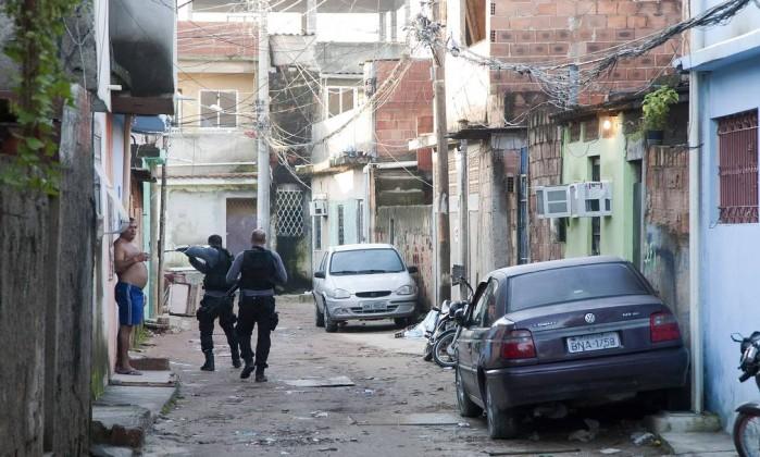 Morador é abordado por policias em uma das ruas da favela Fernando Quevedo / Agência O Globo
