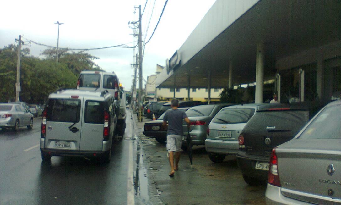 """Estacionamento irregular é comum em frente à concessionária de veículos Brilhauto, na Avenida Dom Helder Câmara, no Cachambi, Zona Norte do Rio. """"Temos de andar no meio da rua, que é perigosíssima"""", reclama leitor Foto de leitor / Eu-Repórter"""