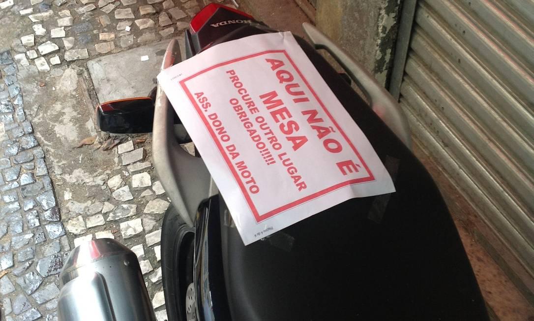 Motorista estaciona motocicleta em cima da calçada na Rua da Conceição, Centro do Rio, e ainda deixa bilhete pedindo educação aos pedestres Foto do leitor Mauro Pauxis / Eu-Repórter