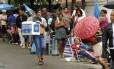 Pessoas na fila observam mulher com kit para venda de cerveja após se cadastrar para trabalhar no carnaval de rua