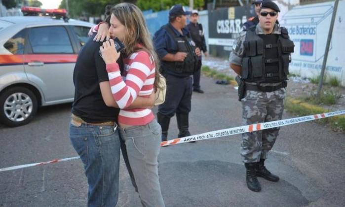 Amigos de vítimas se consolam em área isolada pela polícia local Ronald Mendes/Agencia RBS