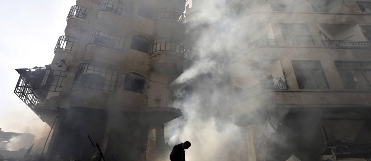 Homem em frente a prédio em chamas depois que a Força Aérea da Síria ataca Ain Tarma, em Damasco Foto: GORAN TOMASEVIC / REUTERS