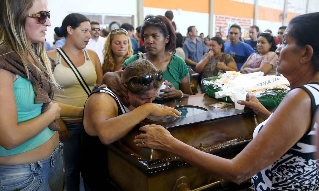 Parente chora diante do caixão de vítima do incêndio em Santa Maria, no Rio Grande do Sul JEFFERSON BERNARDES / AFP