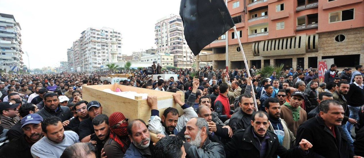 Egípcios carregam os caixões de seis pessoas mortas no domingo durante os protestos em Port Said Foto: - / AFP
