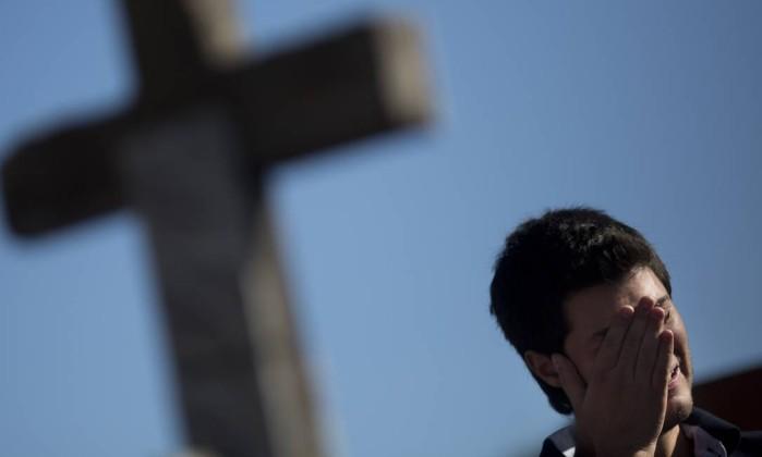 Homem chora no durante enterro de Vinicius Rosado Felipe Dana / AP