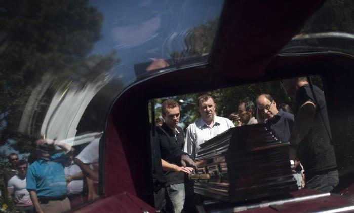 Parentes de vítima retiram caixão de carro de funerária Felipe Dana / AP