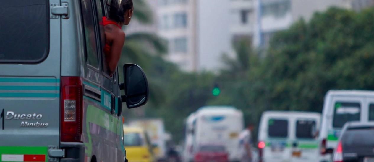 Cobradora com a cabeça para fora de uma van que estaria em situação irregular Foto: Pedro Kirilos / O Globo