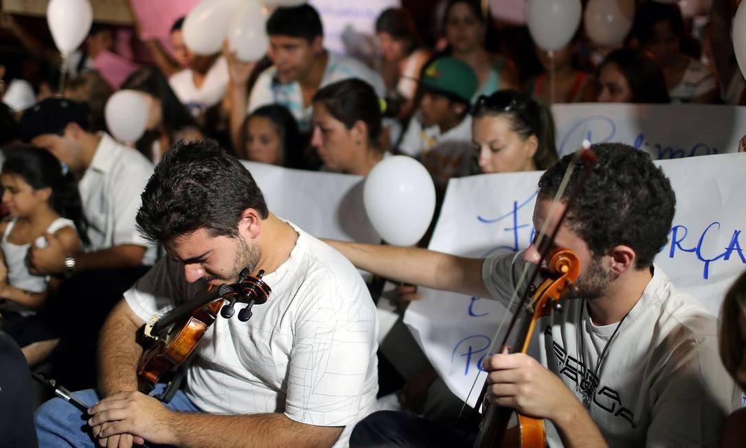 Jovens levam violino em caminhada Foto: JEFFERSON BERNARDES / AFP