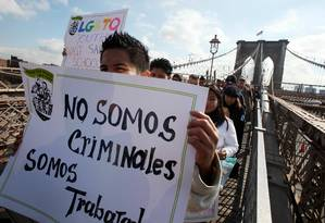 Trabalhadores latinos carregam cartaz 'Não somos criminosos, somos trabalhadores' em passeata por Nova York Foto: MARIO TAMA / AFP