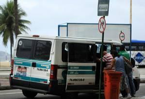 Van realiza embarque de passageiros em ponto de ônibus, prática proibida por lei Foto: Foto: Guilherme Leporace