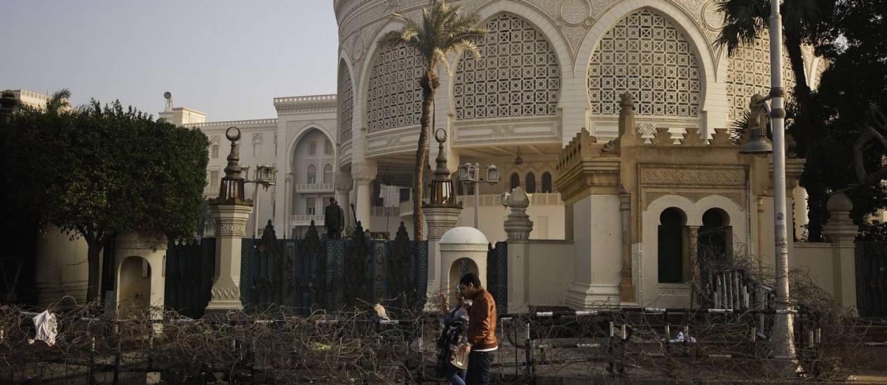 Um egípcio caminha em frente ao palácio presidencial depois de uma noite de confrontos entre policiais e manifestantes no Cairo Foto: GIANLUIGI GUERCIA / AFP