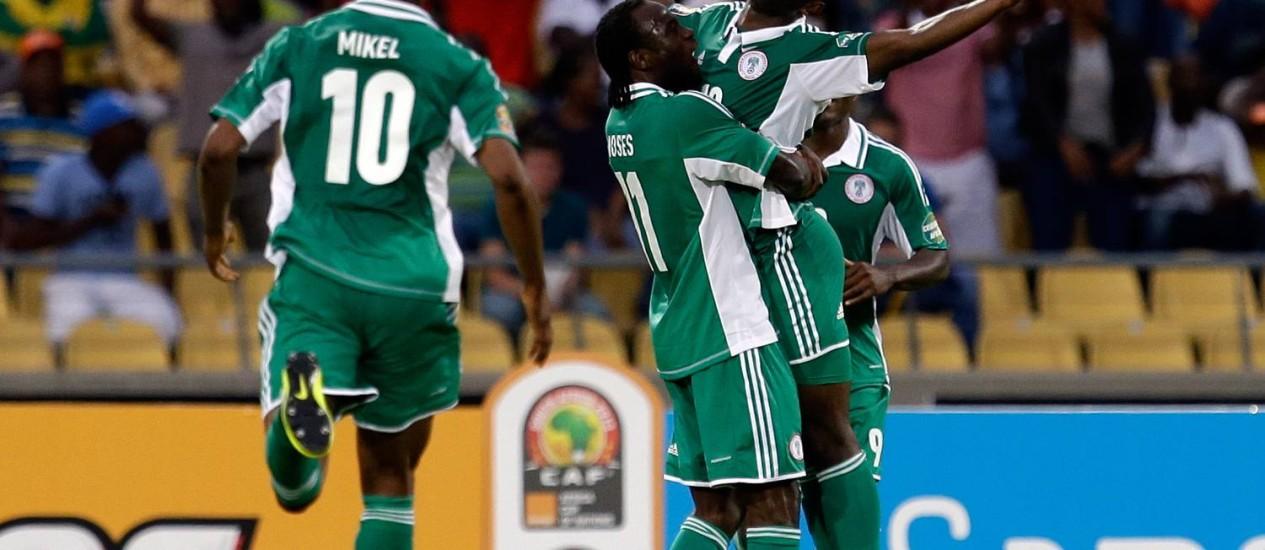 O nigeriano Sunday Mba é erguido pelos colegas após marcar o gol da vitória sobre a Costa do Marfim Foto: Armando Franca / AP