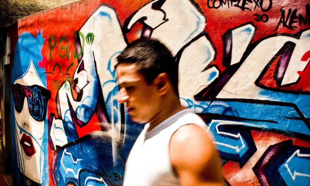 Pedestre passa por muro grafitado no Complexo do Alemão: uma das manifestações artísticas mapeadas pelo projeto Foto: Léo Lima / Divulgação / Imagens do Povo