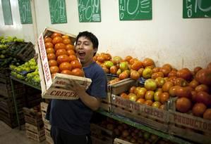 Funcionário de mercado em Buenos Aires carrega tomates: preços congelados até 1º de abril Foto: Victor R. Caivano / AP