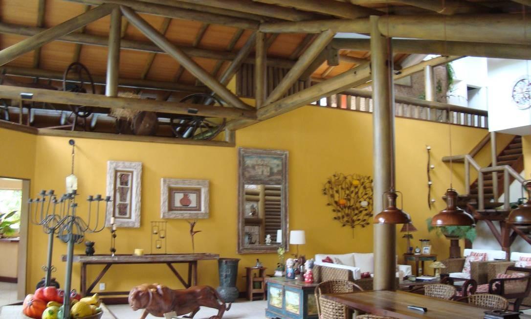 Os tons de madeira e mostarda prevalecem na decoração do ambiente de estar. Tons remetem ao clima serrano, de frio, natureza e aconchego Foto: Divulgação