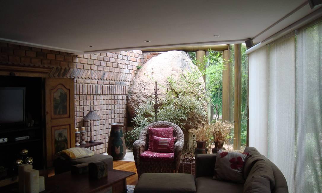 O arquiteto aproveitou uma das grandes pedras encontradas no terreno como parte fundamental da sala, ao transformá-la em parte da parede da casa Foto: Divulgação
