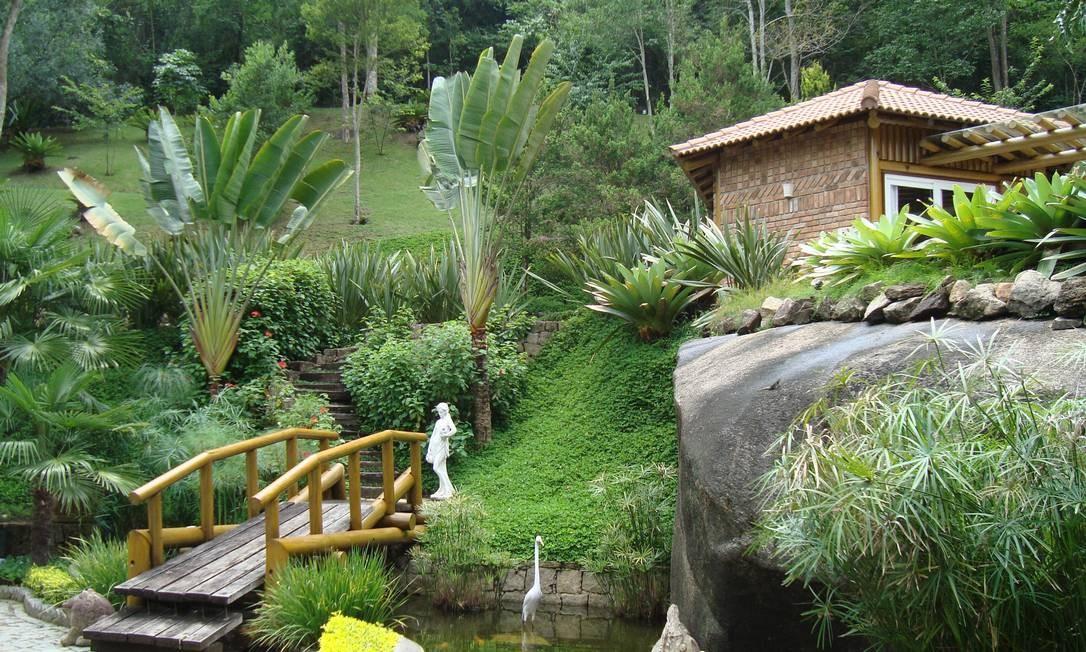 A casa está em sintonia com a natureza. Além da vegetação, há um lago tratado para criação de peixes que a circunda. A ponte reforça o charme das belezas naturais Foto: Divulgação