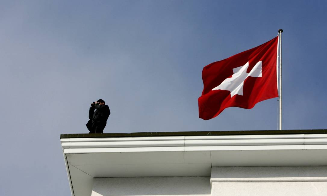 Policial suíço faz vigia ao lado da bandeira do país Foto: Pascal Lauener / Reuters