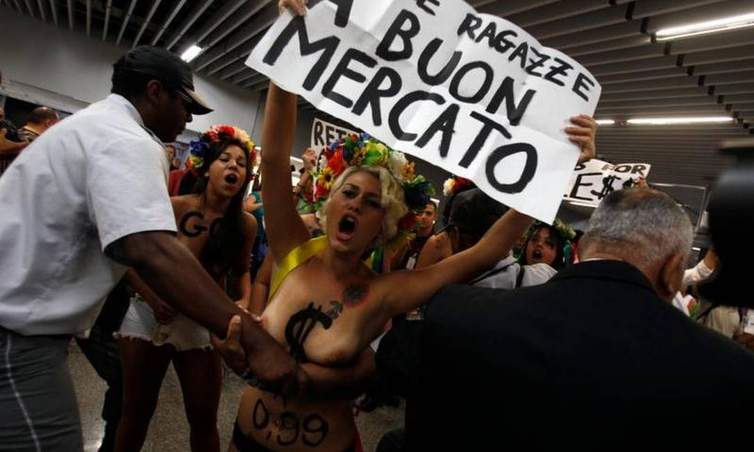 Seguranças tentam impedir protesto de ativistas do Femen Brasil no Galeão AFP / AFP