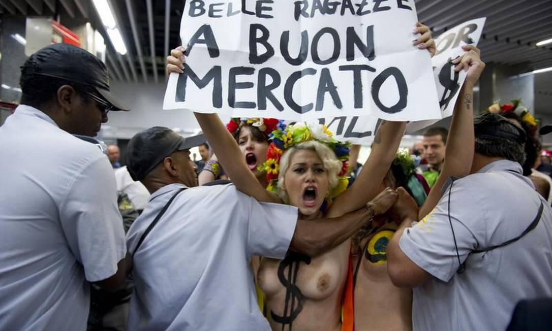 Ativistas do Femen Brasil protestam no Galeão e seguranças tentam impedir; elas levaram cartazes contra o turismo sexual AFP / AFP