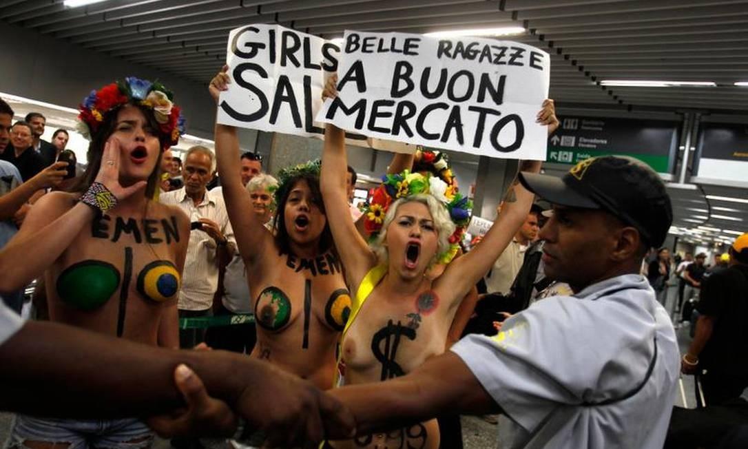 Manifestantes do Femen Brasil pintaram os corpos e levaram cartazes ao Galeão para protestar contra o turismo sexual no Rio durante o carnaval AFP / AFP