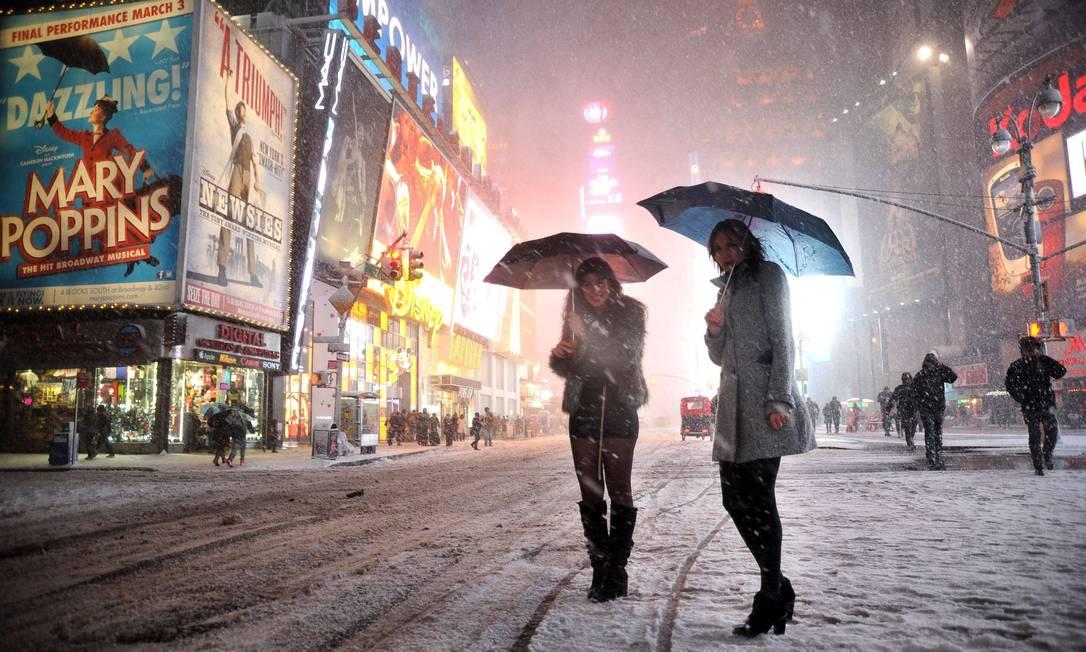 Temendo uma piora do clima, duas garotas buscavam um táxi para deixar a Times Square MEHDI TAAMALLAH / AFP