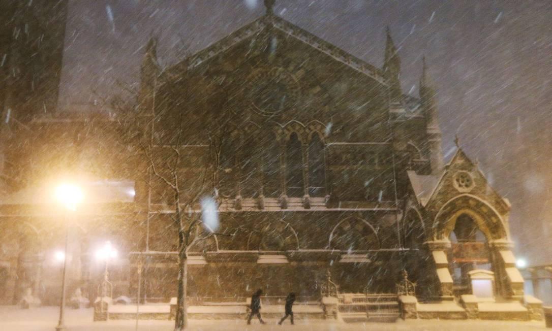 Em Boston, pessoas tentam enfrentar a nevasca em frente a uma igreja do bairro de Back Bay MARIO TAMA / AFP