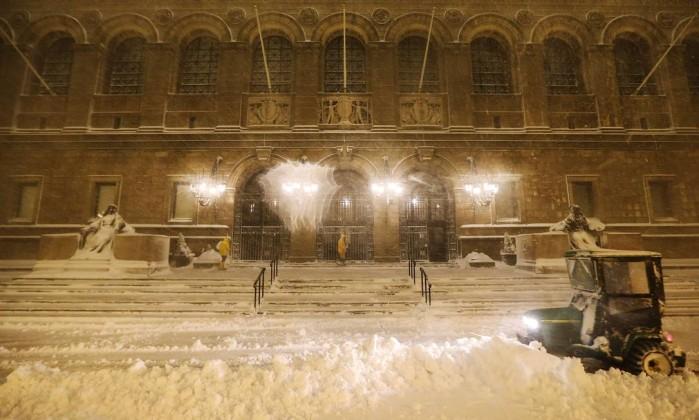 Funcionário tira excesso de neve da frente da biblioteca municipal de Boston, em Massachusetts MARIO TAMA / AFP