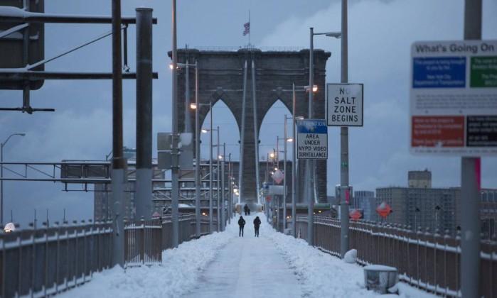 Pedestres caminham pelo Brooklyn Bridge coberta de neve Andrew Kelly / AFP