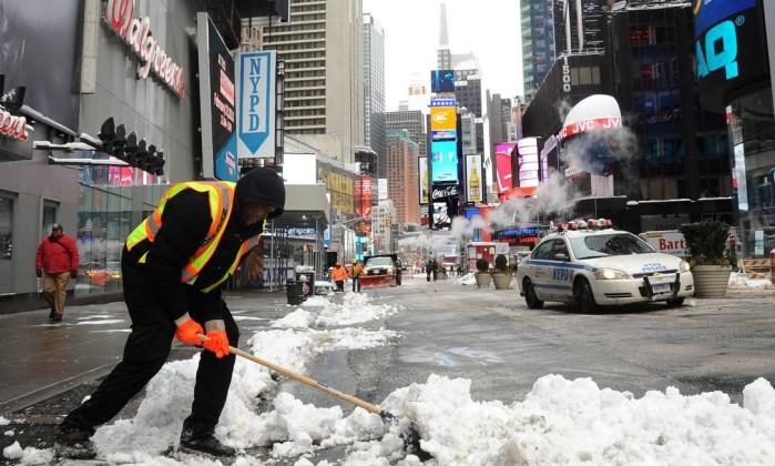 Funcionário retira o gelo da Times Square, área turística mais densa de Nova York MEHDI TAAMALLAH / AFP