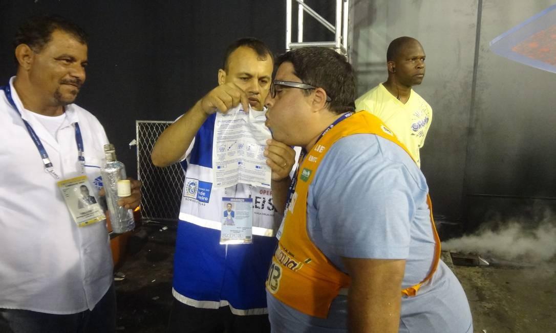 Teste. Repórter Luiz Ernesto Magalhães sopra o bafômetro da Lei Seca após beber cravinho