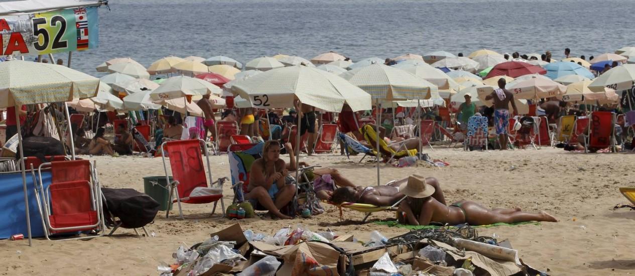Cartão-postal emporcalhado. Na Praia de Ipanema, banhistas dividem espaço com um monte de lixo deixado na areia, um dos problemas do carnaval Foto: Domingos Peixoto / O Globo