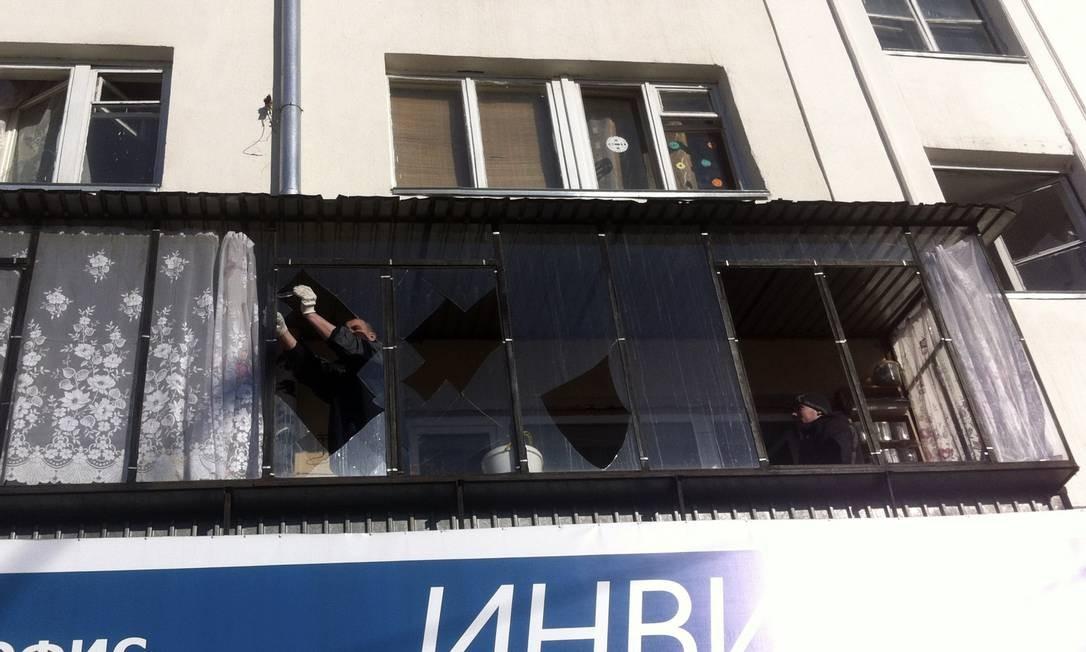Homem remove pedaços de vidro de uma janela, que ficou destruída. A onda de choque provocada pelo fenômeno destruiu janelas e balançou prédios, enquanto equipes de resgate foram deslocadas para socorrer a população Foto: REUTERS