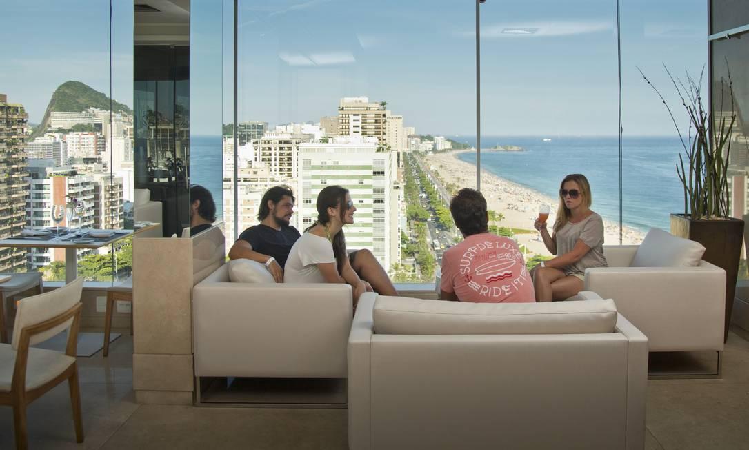 Livian Valias, com um drinque na mão, brinda com amigos tendo toda a Praia de Ipanema como cenário no 7zero6 Agência O Globo / Mônica Imbuzeiro