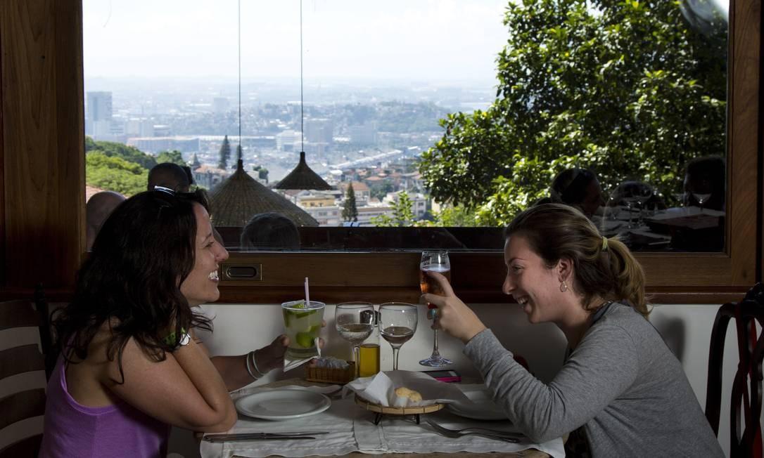A cubana Mariana Carreras e a venezuelana Samantha Stransky brindam a paisagem do Rio vista do Aprazível: visual vai de Santa Teresa e Centro até a Serra dos Órgãos Foto: Agência O Globo / Mônica Imbuzeiro