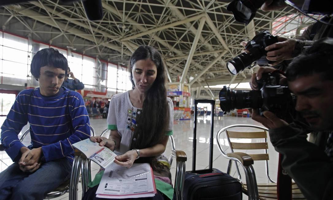 Ao lado do filho Teo, Yoani mostra seu passaporte aos cinegrafistas e jornalistas Foto: AP