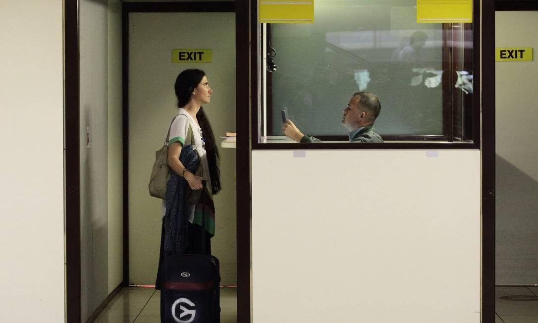 Yoanis apresenta seus documentos no guichê de controle de passaporte do aeroporto de Havana Foto: REUTERS
