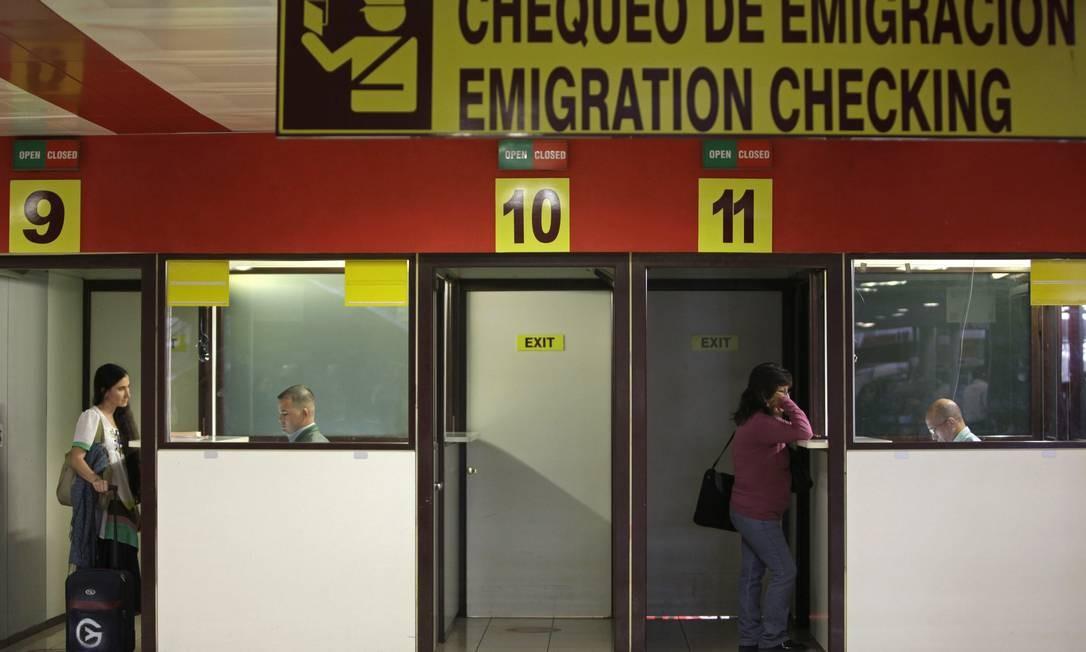 A dissidente cubana entrega seus documentos no guichê da emigração, no Aeroporto de Havana. Foto: AP