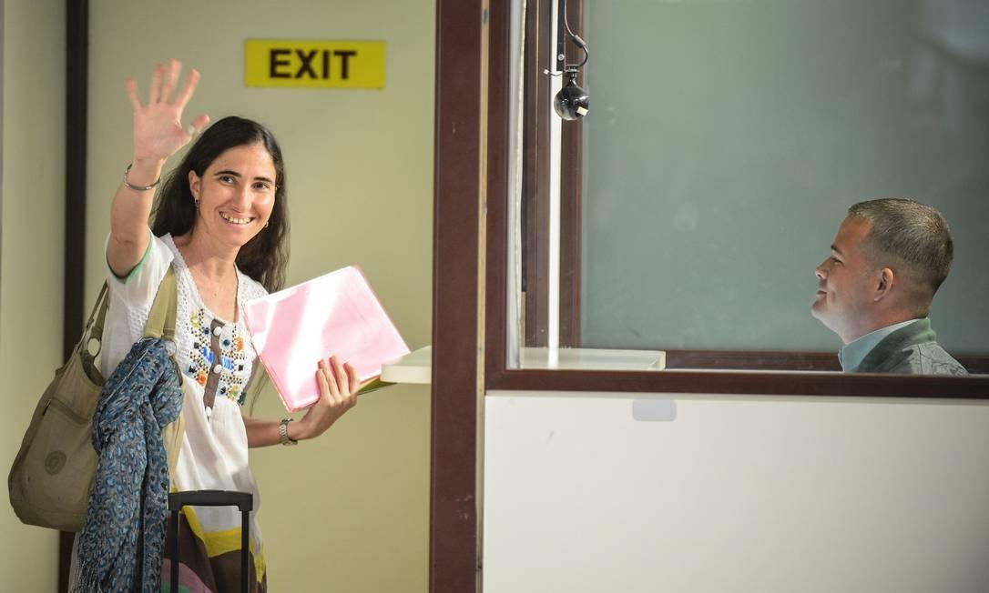 Já a documentação e passaporte em mãos, ela acena para parentes e jornalistas antes de embarcar para o Brasil Foto: AFP
