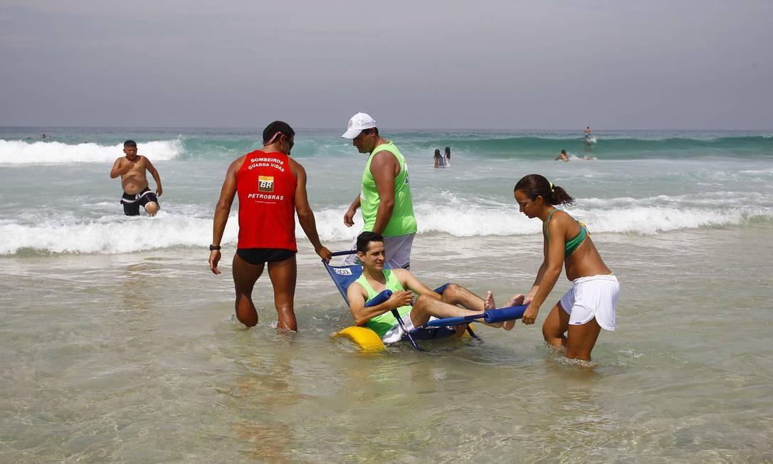 """Banho de mar. Um dos organizadores do """"Praia para todos"""", Fábio Fernandes usa a cadeira anfíbia para entrar na água Foto: Pablo Jacob / O Globo"""