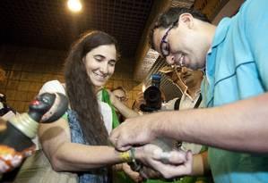 O cineasta Dado Galvão amarra em Yoani uma fita do Nosso Senhor do Bonfim para fazer 3 pedidos Foto: Hans von Manteuffel / Agência O Globo