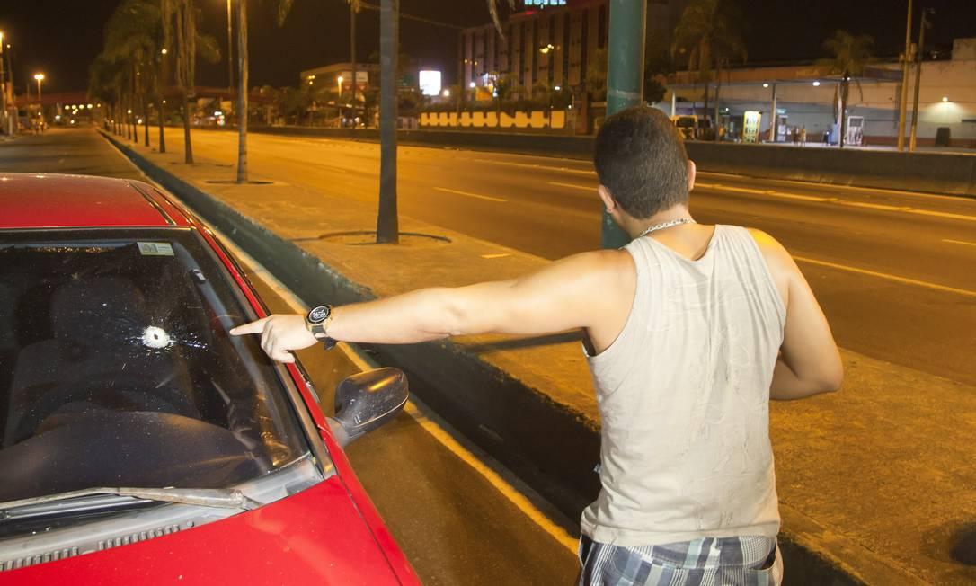 Motorista mostra a marca de tiro que atingiu seu veículo durante ação do Bope no Parque União, pouco antes da operação da prefeitura começar na região Foto: Fernando Quevedo / Agência O Globo