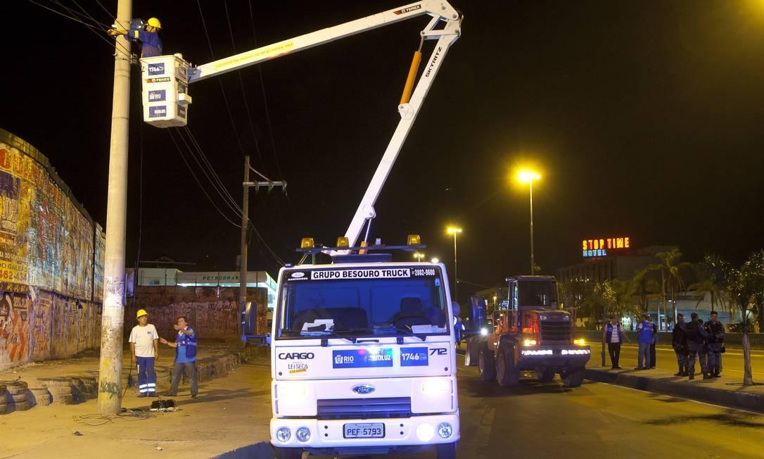 Funcionário da prefeitura prepara poste para instalação de refletor Foto: Fernando Quevedo / Agência O Globo