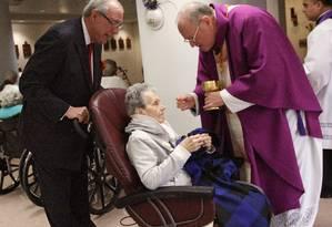 Arcebispo Timothy Dolan oferece a comunhão em um centro de reabilitação em Nova York Foto: Jan Somma-Hammel / AP